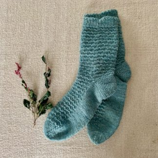 blue hand knit socks on a textured background